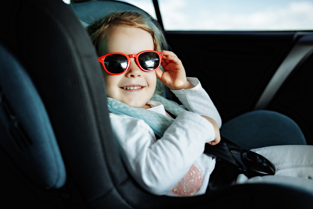 infant in car with red sunglasses