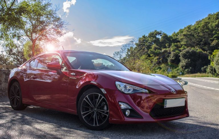 Detailed red Toyota 86 in the sun on public roads.