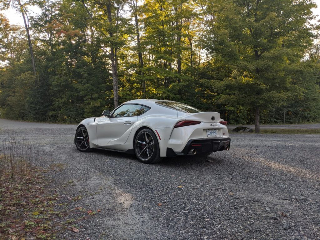 back of white Toyota supra in the woods during fall