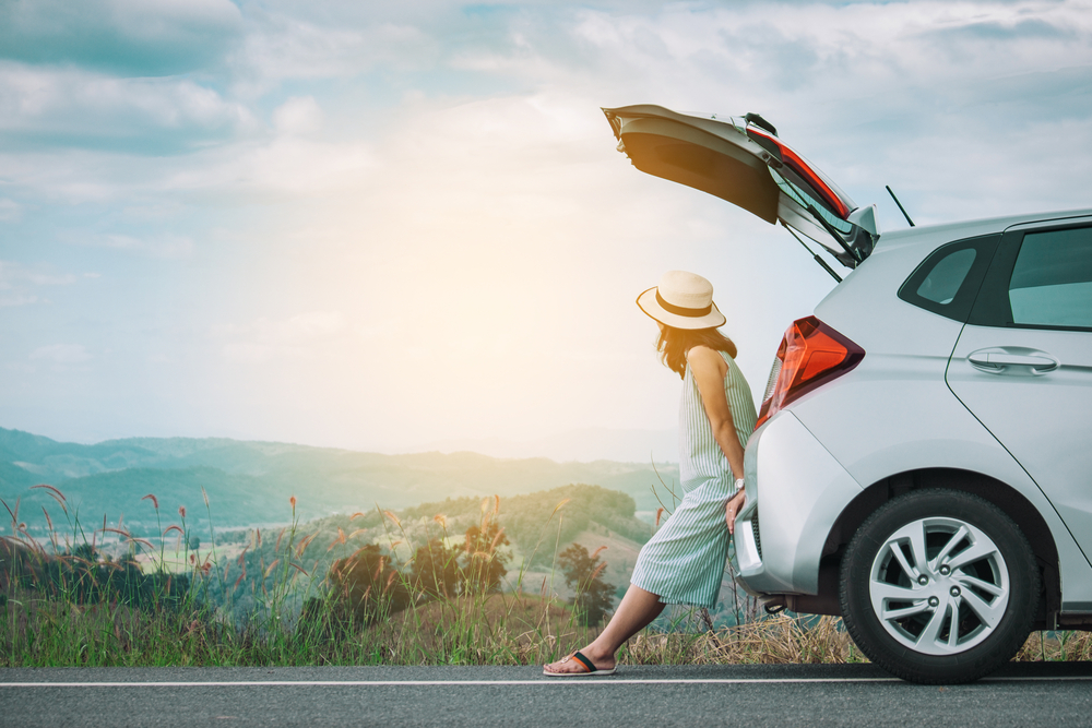 women looking at a landscape sitting in the back of her rental car