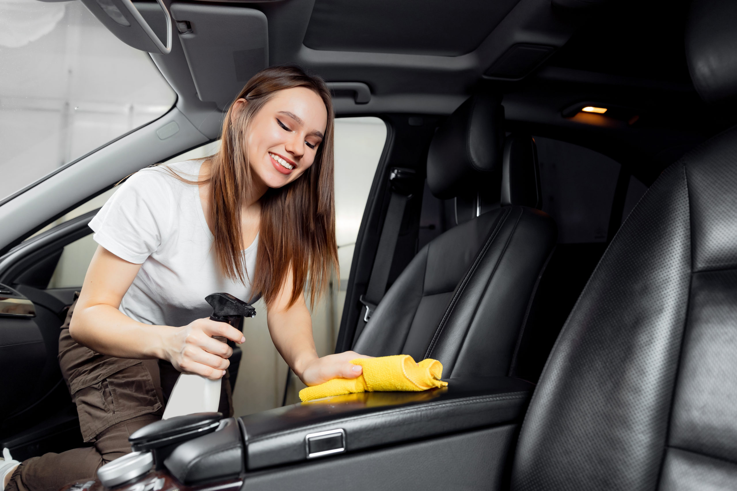 woman cleaning car interior leather